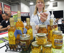 Al Hartmann  |  The Salt Lake Tribune Keli Bess of Slide Ridge Honey located in Mendon Utah pours a sample of honey wine vinegar to taste at the Associated Food Stores Food Show 2012 at the Salt Palace Convention Center Wednesday June 20.  The business makes honey, honey wine vinegar and wine.     The food show includes Utah grown and manufactured products to be seen by  400 grocers doing business in eight states.