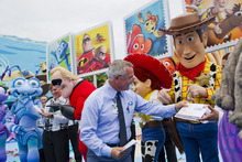 This image released by Disney shows U.S. Postal Service mail carrier Dennis Blase presenting First Day of Issue commemorative stamps to Disney characters at the new Disney's Art of Animation Resort, Friday, June 1, 2012 in Lake Buena Vista, Fla. The stamps feature characters from animated films,