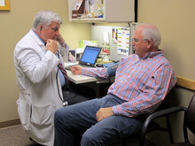 In a June 11, 2012, photo Dr. Glen Stream prepares to examine patient Pete Forsyth in Spokane, Wash. Health care spending has eased up recently, a welcome respite for government and corporate budgets.