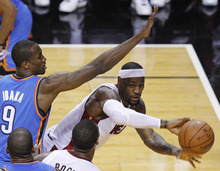 Miami Heat small forward LeBron James (6) passes around Oklahoma City Thunder power forward Serge Ibaka (9) from Republic of Congo during the first half at Game 4 of the NBA finals basketball series, Tuesday, June 19, 2012, in Miami.  (AP Photo/Wilfredo Lee)