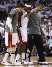 Miami Heat small forward LeBron James (6), center, is helped from the court by Mike Miller, left, and Juwan Howard, right during the second half at Game 4 of the NBA finals basketball series against the Oklahoma City Thunder , Tuesday, June 19, 2012, in Miami. The Heat won 104-98. (AP Photo/Lynne Sladky)