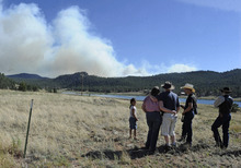 In this June 17, 2012, photo, the Geer family watches from Lake George, Colo., as the Springer Fire burns in the distance. Ten years ago, the family was evacuated during the Hayman Fire near Lake George. (AP Photo/The Colorado Springs Gazette, Jerilee Bennett)