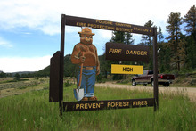 A sign warns  of fire danger along a county road east of Red Feather Lakes, Colo., on Sunday, June 17, 2012, as a stubborn wildfire continues to burn in northern Colorado. Crews are facing powerful winds as they battle the blaze that has scorched about 86 square miles of mountainous forest land and destroyed at least 181 homes, the most in state history. (AP Photo/David Zalubowski) (AP Photo/David Zalubowski)