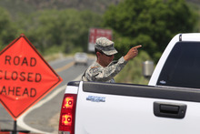 A National Guardsman stops a motorist from driving down Highway 14 north of Laporte, Colo., on Sunday, June 17, 2012, as a stubborn wildfire continues to burn in northern Colorado. Crews are facing powerful winds as they battle the blaze that has scorched about 86 square miles of mountainous forest land and destroyed at least 181 homes, the most in state history. (AP Photo/David Zalubowski)