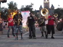 The Stooges Brass Band performs on the street, between Washington Square and Library Square, as part of a