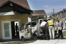 Scott Sommerdorf     The Salt Lake Tribune              Sandy Fire inspectors look at the aftermath of a fire associated with a vehicle that exploded, and caused a small fire at the home at 8933 Heights Drive in Sandy, Thursday, June 21, 2012. The vehicle exploded and launched itself from the parking spot in the foreground to a spit up against the beam of the home. The heat of the vehicle fire caused the damage to the home.