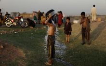 An Afghan refugee youth, center, pours water on himself to cool off, while other refugees are seen collecting water, on World Refugee Day, in a slum on the outskirts of Islamabad, Pakistan, Wednesday, June 20, 2012. The Pakistani government and the United Nations refugee agency reached an agreement in March 2009 to allow some 1.7 million registered Afghan refugees living in Pakistan to continue sheltering there until at least 2012, thousands of them still live without electricity, running water and other basic services. (AP Photo/Muhammed Muheisen)