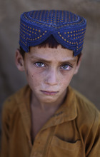 Afghan refugee Ibraheem Rahees, 6, is seen in a slum, on World Refugee Day, on the outskirts of Islamabad, Pakistan, Wednesday, June 20, 2012. The Pakistani government and the United Nations refugee agency reached an agreement in March 2009 to allow some 1.7 million registered Afghan refugees living in Pakistan to continue sheltering there until at least 2012, thousands of them still live without electricity, running water and other basic services. (AP Photo/Muhammed Muheisen)