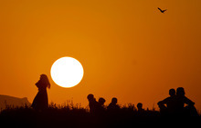 Afghan refugee youth are silhouetted against the sunset as they gather at a slum on World Refugee Day on the outskirts of Islamabad, Pakistan on Wednesday, June 20, 2012. World Refugee Day, a day initiated by the United Nations to raise awareness on the plight of refugees worldwide, is observed on June 20 every year.(AP Photo/Anjum Naveed)