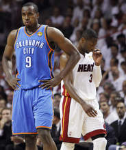 Oklahoma City Thunder power forward Serge Ibaka (9) from Republic of Congo and Miami Heat shooting guard Dwyane Wade (3) react during the first half at  Game 5 of the NBA finals basketball series, Thursday, June 21, 2012, in Miami. (AP Photo/Lynne Sladky)