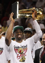 Miami Heat shooting guard Dwyane Wade holds the the Larry O'Brien NBA Championship Trophy after Game 5 of the NBA finals basketball series against the Oklahoma City Thunder, Friday, June 22, 2012, in Miami. The Heat won 121-106 to become the 2012 NBA Champions. (AP Photo/Lynne Sladky)