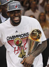 Miami Heat small forward LeBron James celebrates with the most valuable player trophy after Game 5 of the NBA finals basketball series against the Oklahoma City Thunder, Friday, June 22, 2012, in Miami. The Heat won 121-106 to become the 2012 NBA Champions. (AP Photo/Lynne Sladky)