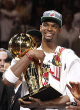 Miami Heat power forward Chris Bosh holds the the Larry O'Brien NBA Championship Trophy after Game 5 of the NBA finals basketball series against the Oklahoma City Thunder, Friday, June 22, 2012, in Miami. The Heat won 121-106 to become the 2012 NBA Champions.(AP Photo/Lynne Sladky)