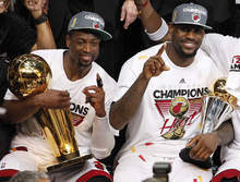 The Miami Heat's Dwyane Wade holds the the Larry O'Brien NBA Championship Trophy and LeBron James holds his most valuable player trophy after Game 5 of the NBA finals basketball series against the Oklahoma City Thunder, Friday, June 22, 2012, in Miami. The Heat won 121-106 to become the 2012 NBA Champions. (AP Photo/Lynne Sladky)