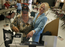 Scott Sommerdorf  |  The Salt Lake Tribune              Election Judge Blythe Carlsen, right, helps voter Roxane Jensen navigate touch-screen voting machine at the Eddie P. Mayne Kearns Senior Center in Kearns. The Salt Lake County Clerk's Office has had to add election judges, especially Spanish-speaking judges, for the primary on Tuesday.
