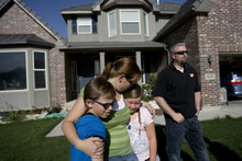 Kim Raff | The Salt Lake Tribune Jill Derington hugs her children (left) Jacob and Amara Derington outside their home in the Saratoga Springs subdivision in Saratoga Springs, Utah on June 23, 2012. The Derington's evacuated from their home due to the Dump Wildfire in Saratoga Springs-Eagle Mountain area but were able to return.