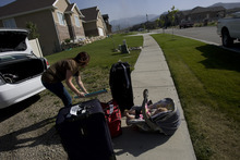 Kim Raff | The Salt Lake Tribune Chelsea Coon unpacks her car while her daughter Lylah Coon sits in her car seat in Saratoga Springs, Utah on June 23, 2012. Coon was visiting her parents house when they were evacuated due to the Dump Wildfire in Saratoga Springs-Eagle Mountain.  Evacuated residents were able to return to their homes.