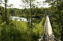 FILE - This July 27, 2003, file photo, shows a suspension bridge over the Manistee River southeast of Mesick, Mich., where the North Country Scenic Trail follows the river for miles. The North Country National Scenic Trail runs 4,600 miles from North Dakota to New York's eastern border. From there, it's about 40 miles across Vermont fields and mountains to the Appalachian Trail. Closing the 40-mile gap is a priority for the Michigan-based North Country Trail Association, the group responsible for the trail. (AP Photo/John L. Russell, File)