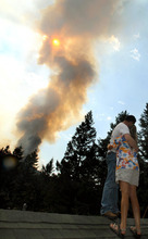 Greg Bodine hugs his wife, Karen Bodine, as they watch a wildfire burn from the roof of her parents' home in Cascade, Colo., on Sunday, June 24, 2012. The fire erupted and grew out of control to more than 3 square miles early Sunday, prompting the evacuation of more than 11,000 residents and an unknown number of tourists. (AP Photo/The Colorado Springs Gazette, Christian Murdock)