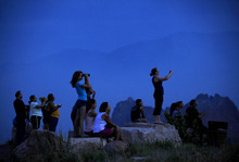 People watch from Mesa Road as a wildfire continues to burn west of Colorado Springs, Colo. on Sunday, June 24, 2012. The fire erupted Saturday and grew out of control to more than 3 square miles early Sunday, prompting the evacuation of more than 11,000 residents and an unknown number of tourists. (AP Photo/The Colorado Springs Gazette, Susannah Kay)