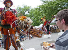 Michael Mangum  |  Special to the Tribune  A performer on stilts controls a hand-powered wooden creature and pretends to nibble on the dinner of Bountiful resident Sam Mortenson at the Utah Arts Festival in downtown Salt Lake City on Sunday, June 24, 2012.