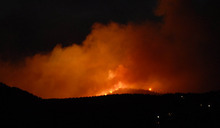 The evening sky glows orange as smoke and flames from the Waldo Canyon Fire has consumed 2500 acres west of Garden of the Gods near Colorado Springs, Colo. on Saturday, June 23, 2012.  The fire is zero percent contained. Voluntary and mandatory evacuations were taking place across the west side of Colorado Springs.  Tankers were dropping fire retardant in front of the advancing flames.  ( AP Photo/Bryan Oller)