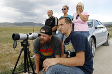 Al Hartmann  |  The Salt Lake Tribune   Jed Buys, left, and his brother Jordan share a look through a spotting scope to look at the family's burned cabin high on the mountain near Indianola.  Craig, Cassie and Cindy Buys behind them reflect on the good times they had in the cabin.  It was one of eight cabins in the Indian Ridge homeowners assoication that burned in the Wood Hollow fire.  The family built the cabin together in 2001.  It was their first look at the damage.  All that's let is the foundation.