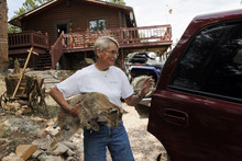 Shirley Paskett loads her stuffed bob cat into her vehicle after she and her partner were evacuated from their home after the High Park wildfire crossed to the north side of Poudre Canyon the Glacier View area near Livermore, Colo., on Friday, June 22, 2012.  The fire is burning on more than 68,000 acres west of Fort Collins and has destroyed at least 189 homes. (AP Photo/Ed Andrieski)
