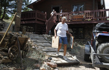 Shirley Paskett, front, and her partner Pam Creech evacuate their home after the High Park wildfire crossed to the north side of Poudre Canyon the Glacier View area near Livermore, Colo., on Friday, June 22, 2012.  The fire is burning on more than 68,000 acres west of Fort Collins and has destroyed at least 189 homes (AP Photo/Ed Andrieski)