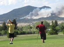 A golfer tees off as his partner watches a wildfire burning in the Scratchgravel Hills on Monday, June 25, 2012, in Helena, Mont. Scorching heat and high winds caused wildfires to break out across southwestern Montana, forcing the evacuation of more than 200 homes. (AP Photo/Matt Volz)