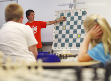 Lennie Mahler  |  The Salt Lake Tribune Kayden Troff, 14, instructs young chess players how to keep pieces coordinated to block opponents' moves during a lesson at the McGillis School on Monday, June 25, 2012. Troff was selected for the