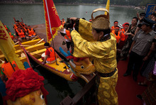 A Chinese actor dressed in an emperor costume pours rice dumplings near the dragon boats during a religious ritual to honor Chinese poet Qu Yuan during the Duanwu Festival at Longtan park in Beijing, China Saturday, June 23, 2012. Rice dumplings are traditionally eaten during the Duanwu festival, also known as the Dragon Boat festival, which falls on the fifth day of the fifth month of the Chinese calendar, commemorating the death of Qu Yuan, a famous Chinese poet from the kingdom of Chu who lived during the Warring States period. (AP Photo/Andy Wong)
