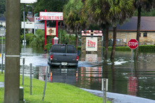 A motorist travels through floodwaters on Silver Springs Boulevard, Monday, June 25, 2012, in Salt Springs, Fla. Tropical Storm Debby raked the Tampa Bay area with high wind and heavy rain Monday in a drenching that could top 2 feet over the next few days and trigger widespread flooding. (AP Photo/The Ocala Star-Banner, Alan Youngblood)