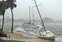 A sailboat that broke free from it's mooring is pushed against a sea wall at Bayfront Park in Sarasota, Fla. by winds from Tropical Storm Debby on Monday, June 25, 2012. Tropical Storm Debby drenched Florida with heavy rains, flooded low-lying neighborhoods and knocked out power to thousands of homes and businesses as it lingered off the state's coast Monday. (AP Photo/Sarasota Herald-Tribune, Mike Lang)  CHARLOTTE SUN OUT, BRADENTON HERALD OUT, MAGS OUT, TV OUT, INTERNET OUT, NO SALES