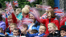 Members of the public wave their Union Jack flags as they wait for Britain's Queen Elizabeth II to arrive for a Service of Thanksgiving in Saint Macartin's Cathedral in Enniskillen, Northern Ireland, Tuesday, June 26, 2012. The Queen and the Duke of Edinburgh arrived in Northern Ireland for a two day visit to mark the Queen's Diamond Jubilee. (AP Photo/Peter Morrison)