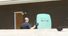 Lennie Mahler  |  The Salt Lake Tribune Police search a garbage can in a backyard as they investigate the neighborhood near a canal where the body of a 6-year-old was found Tuesday, June 26, 2012.