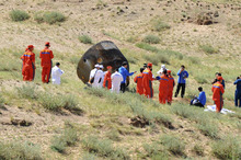 In this photo released by China's Xinhua News Agency, members of the search team approach the re-entry capsule of China's Shenzhou 9 spacecraft in Siziwang Banner of north China's Inner Mongolia Autonomous Region, June 29, 2012. The Chinese space capsule with three astronauts aboard returned Friday from a 13-day mission to an orbiting module that is a prototype for a future permanent station. (AP Photo/Xinhua, Ren Junchuan) NO SALES