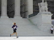 Fox News Channel reporter Shannon Bream is seen sprinting across the steps of the Supreme Court after the released of the court's decision on Arizona's controversial immigration law known as SB 1070, Monday, June 25, 2012 in Washington. The court's decision on Monday upheld the part of the law that allows officers to check the status of someone suspected of being in the U.S. illegally. (AP Photo/Pablo Martinez Monsivais)