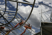 Scott Sommerdorf  |  The Salt Lake Tribune              Workers finish off some iron work at the The Outlets at Traverse Mountain prior to a press conference where an announcement of an expansion and new retailers was made, Thursday, June 28, 2012.