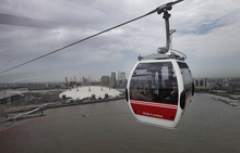 Backdropped by the O2, a Transport for London's gondola lift cable car is seen across the River Thames, in London, Thursday, June 28, 2012. The cable car will make the half-mile (one kilometer) crossing between Greenwich and the Royal Docks, allowing visitors to take in the views of Olympic Park, the Canary Wharf financial center and the Thames Barrier. Each of the 34 cars holds 10 people and looks like the gondolas that ferry skiers up the mountains in the Swiss Alps. Travelers can go one way or round-trip, with a one-way ticket costing 3.20 pounds (5 US dollars). (AP Photo/Lefteris Pitarakis)