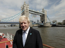 Mayor of London, Boris Johnson, poses for the photographers backdropped by the Olympic rings atop the iconic Tower Bridge in London, after they were lowered into position, coinciding with one month to go until the start of London 2012 Games, Wednesday, June 27, 2012. The giant rings, which are fully retractable to allow for tall ships to pass through the bridge, will remain in position for the duration of the Games. (AP Photo/Lefteris Pitarakis)