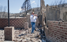 Michael Mangum  |  Special to the Tribune  Indianola resident Dave Taylor takes photos of what is left of his home in Sanpete county on Wednesday, June 27, 2012. The Wood Hollow wildfire ripped through the are earlier in the week and completely destroyed everything on his property.