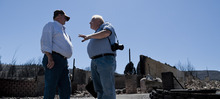 Michael Mangum  |  Special to the Tribune  Indianola resident Dave Taylor, left, and independent insurance adjuster Jeff Selmos discuss insurance claims in front of what is left of Taylor's home on Wednesday, June 27, 2012. The Wood Hollow wildfire ripped through the area earlier in the week, destroying everything on Taylor's property.