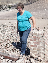 Michael Mangum  |  Special to the Tribune  Indianola resident Janice Taylor walks through the rubble of her home on Wednesday, June 27, 2012. Taylor's home had been completely destroyed when the Wood Hollow wildfire ripped through the area, destroying everything on her property.