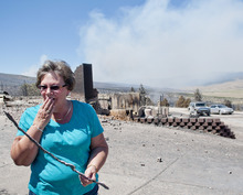 Michael Mangum  |  Special to the Tribune  With smoke from the Wood Hollow wildfire still billowing in the background, Indianola resident Janice Taylor reacts as she walks through her property after flames completely engulfed and destroyed her home and everything on the property on Wednesday, June 27, 2012.
