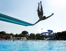 Zach Loken of Winona, Minn., does a flip off of one of the diving boards at the Bob Welch Aquatic Center in Winona on Wednesday, June 27, 2012. Loken, who doesn't normally mind the heat, said it was just