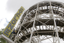 In a Tuesday, June 26, 2012 photo made at Coney Island in New York,  a maintenance worker inspects the Cyclone roller coaster sign.  The New York City landmark and international amusement icon will be feted Saturday, June 30 with a birthday party in its honor.  (AP Photo/Mary Altaffer)