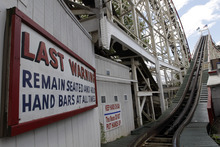 In a Tuesday, June 26, 2012 photo taken on Coney Island in New York, warning signs are posted before the first and steepest climb of the Cyclone roller coaster.  The New York City landmark and international amusement icon will be feted Saturday, June 30 with a birthday party in its honor.  (AP Photo/Mary Altaffer)