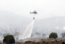 Christopher Reeves  |  Special to The Salt Lake Tribune  A helicopter fights the fire near Saratoga Springs and Eagle Mountain on Friday, June 22, 2012.