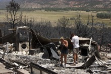 Leah Hogsten  |  The Salt Lake Tribune Amy Beattie and her father, Bruce Beattie, sift through the charred remains of Bruce's home Friday, June 29, 2012 in New Harmony.